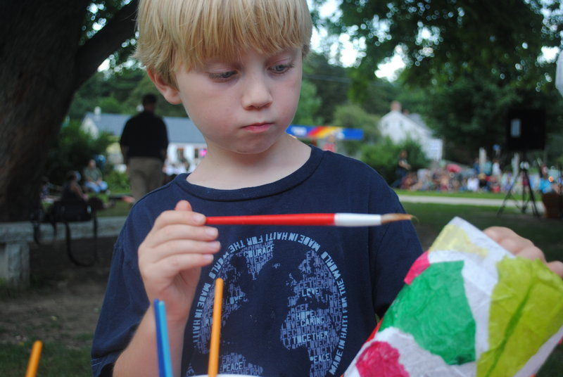 Ashton Gagnon, 7, of Rochester, N.H., makes a paper lantern to be displayed Thursday at LanternFest in South Berwick.