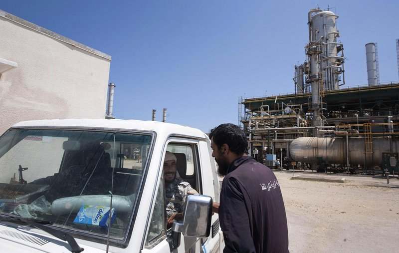 A Libyan oil worker talks with two rebels patrolling a refinery controlled by the anti-Gadhafi forces near Zawiya. Before the uprising, Libya was the world's 12th-largest oil exporter.