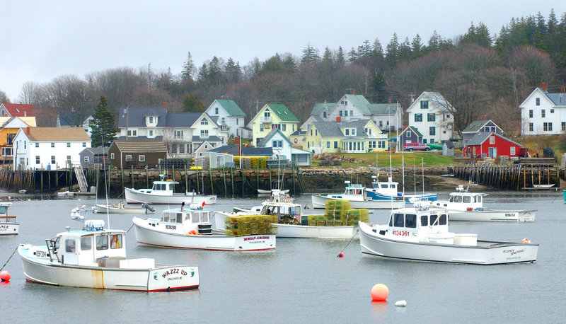 Carver's Harbor on Vinalhaven is filled with lobster boats, with the buildings of village in the background.