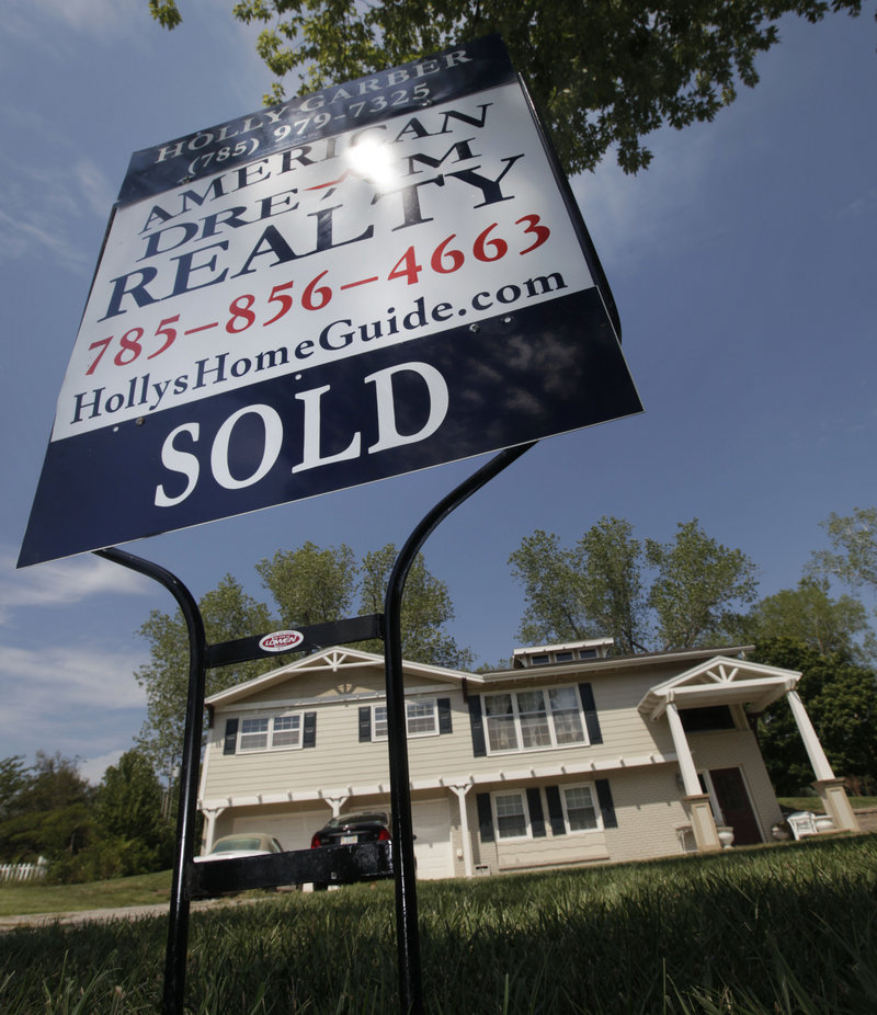 A sold sign stands in front of a home in Lawrence, Kan. The troubled housing market is hurting the broader economy.