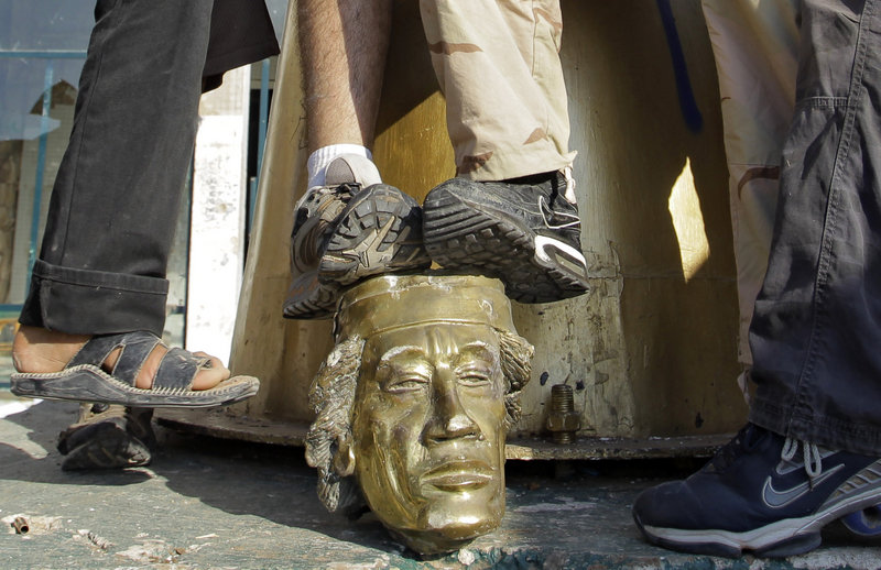 Rebel fighters trample on the head that was broken off a statue of Moammar Gadhafi inside the leader's main compound in Tripoli on Tuesday.