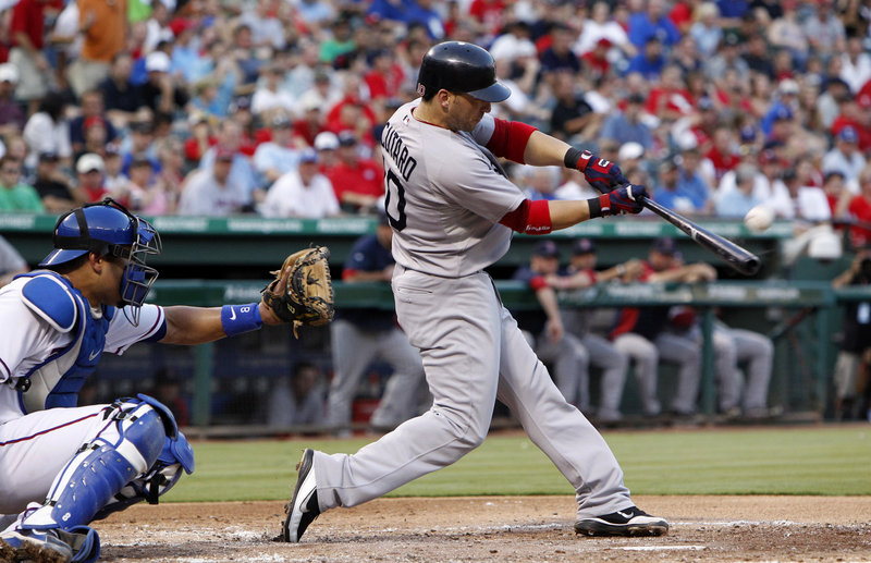Boston Red Sox shortstop Marco Scutaro (10) hits an RBI single in front of Texas Rangers catcher Yorvit Torrealba during the second inning of the baseball game in Arlington, Texas, on Tuesday.