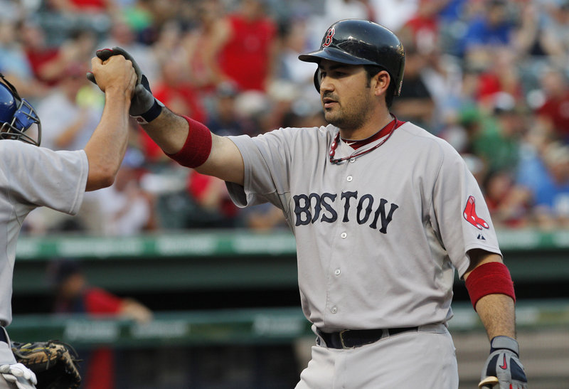 Adrian Gonzalez is greeted at home plate after hitting the first of his two home runs for the Red Sox. This one also scored Jacoby Ellsbury.
