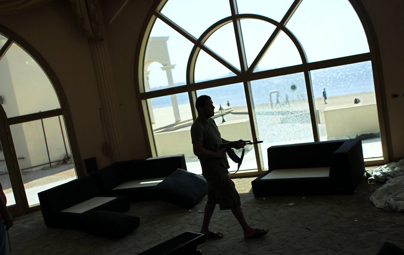 A rebel fighter walks inside the house of Al-Saadi Gadhafi, the son of Libyan dictator Moammar Gadhafi in Tripoli, Libya. Libyans hunting Moammar Gadhafi offered a $2 million bounty on the fallen dictator's head and amnesty for anyone who kills or captures him as rebels battled Wednesday to clear the last pockets of resistance from the capital, Tripoli.