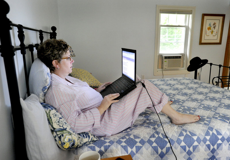 Rabbi Alice Goldfinger, who is recovering from a brain injury, works on a post for her blog, Brainstorm, in her bedroom at her home in Falmouth.