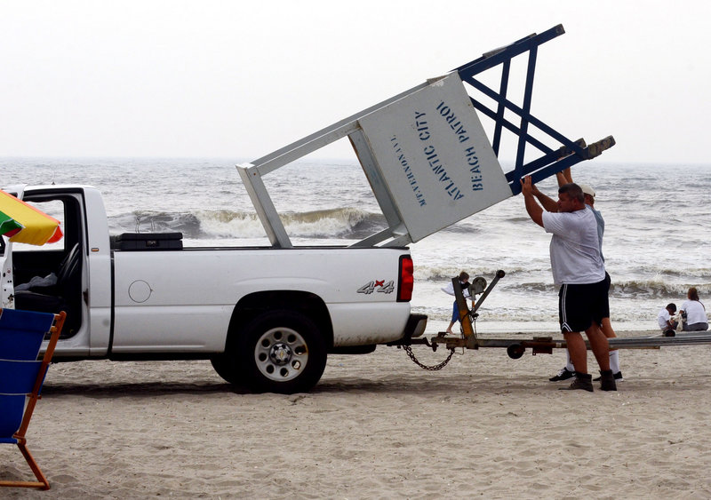Lifeguard John Malecki and Lt. John Ammerman put a lifeguard stand in a pickup truck Thursday as they clear the beach in Atlantic City, N.J., ahead of Hurricane Irene.
