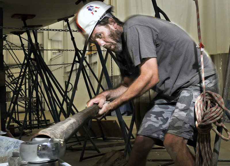 Darrin Low uses a bar to get extra tourque as he works on the Baraka, a lightweight racer-cruiser, at Lyman-Morse Boatbuilders in Thomaston. In the last 30 years, Lyman-Morse has launched nearly 100 vessels, most ranging from roughly 25 feet to 60 feet in length.
