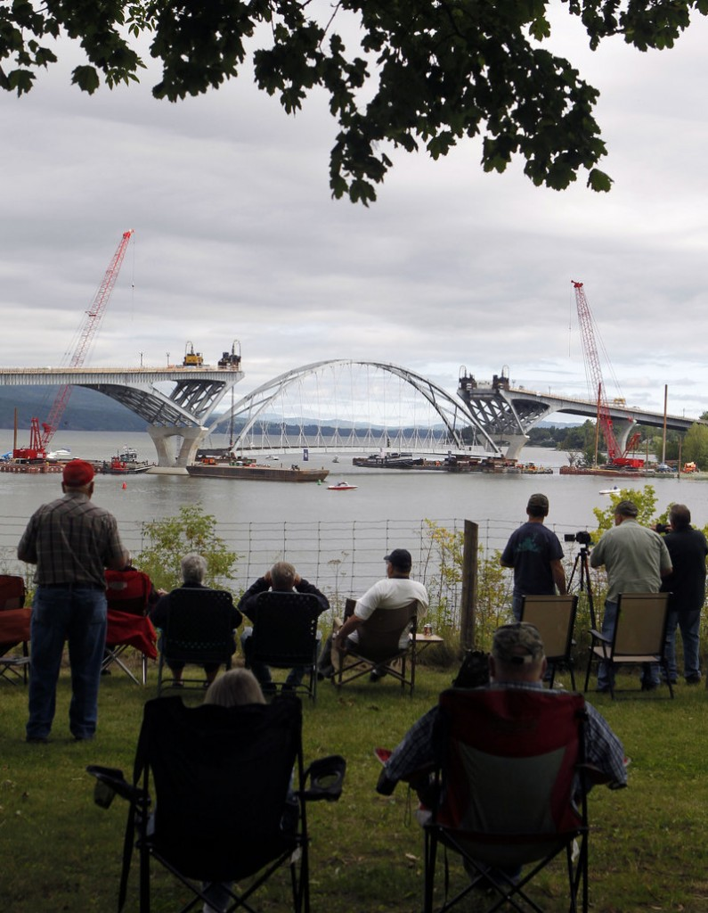 People in Crown Point, N.Y., watch Friday as the center arch of the Lake Champlain Bridge linking Crown Point and Addison, Vt., is positioned before being lifted into place.