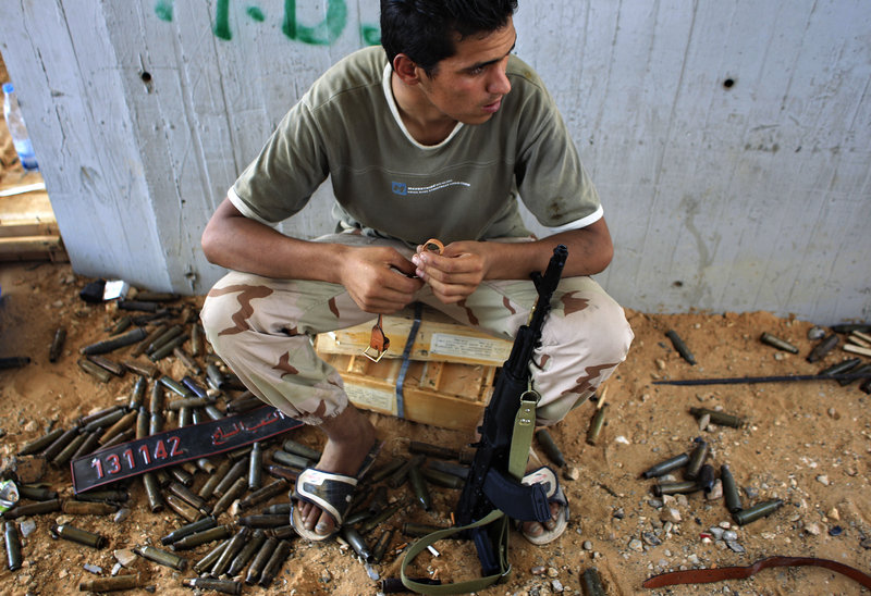 A rebel fighter sits at the checkpoint near the Tripoli International Airport outside Tripoli, LIbya, on Friday. At least 230 were killed and hundreds wounded in the five-day takeover.
