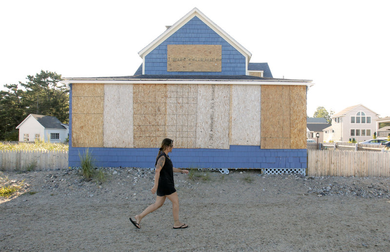 A woman walks past a boarded-up home along Surf Avenue in Saco on Friday. A few houses in the area, which was pounded by a nor'easter on Patriots Day in 2007, were boarded up in preparation for Hurricane Irene.