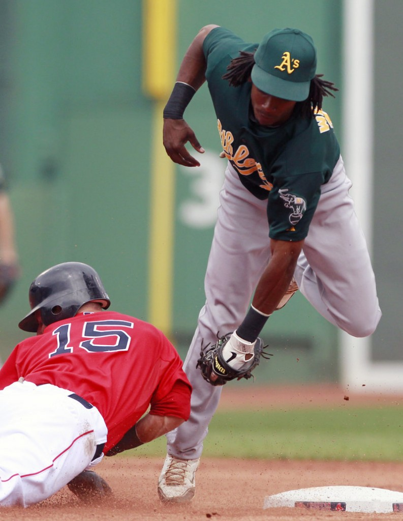Dustin Pedroia of the Red Sox gets tagged out by Oakland second baseman Jemile Weeks trying to stretch a single into a double during Boston's 9-3 win in Game 1 of a doubleheader.