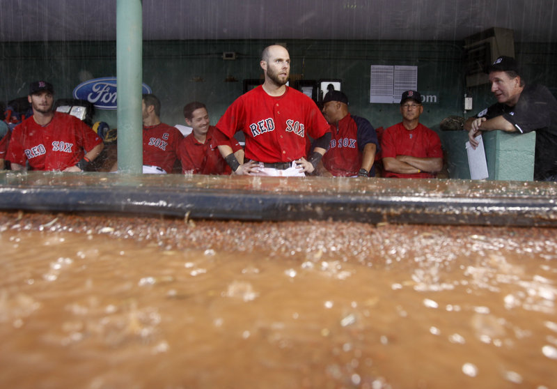 Dustin Pedroia gets a good look at the rain as the Red Sox take shelter in the dugout during a seventh-inning rain delay Saturday in the opener of a doubleheader with the A's.