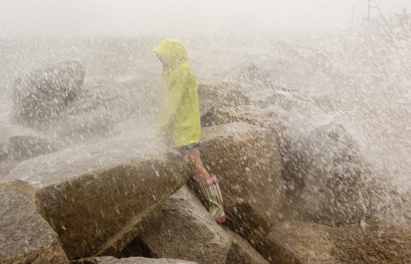 Sarah Casey, 10, of Saco gets soaked by the spray of a wave at high tide on Surf Street in Saco during Hurricane Irene on Sunday.