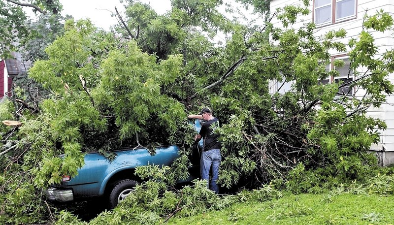 Joe Fox surveys the damage to his 1997 Ford truck after a tree fell on it Sunday at his home on Vigue Street in Waterville. Fox believes the high wind from Tropical Storm Irene toppled the tree.