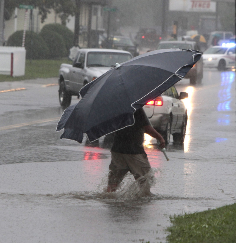 A pedestrian uses a beach umbrella to keep off the rain from Tropical Storm Irene on Sunday in Barre, Vt. Elsewhere in the state, a young woman was missing after she was swept away by the Deerfield River in the southern Vermont town of Wilmington.