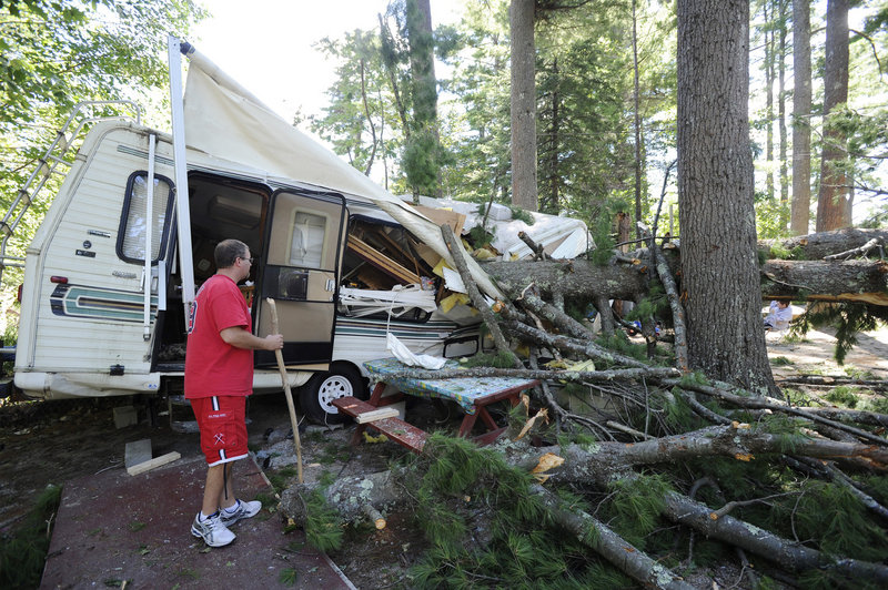 Matthew Fletcher checks the damage done to his 28-foot camper when a pine tree fell during Sunday's storm along Sebago Lake. Fletcher and his fiancee, from Canton, Mass., had left the camper several hours earlier to seek shelter.