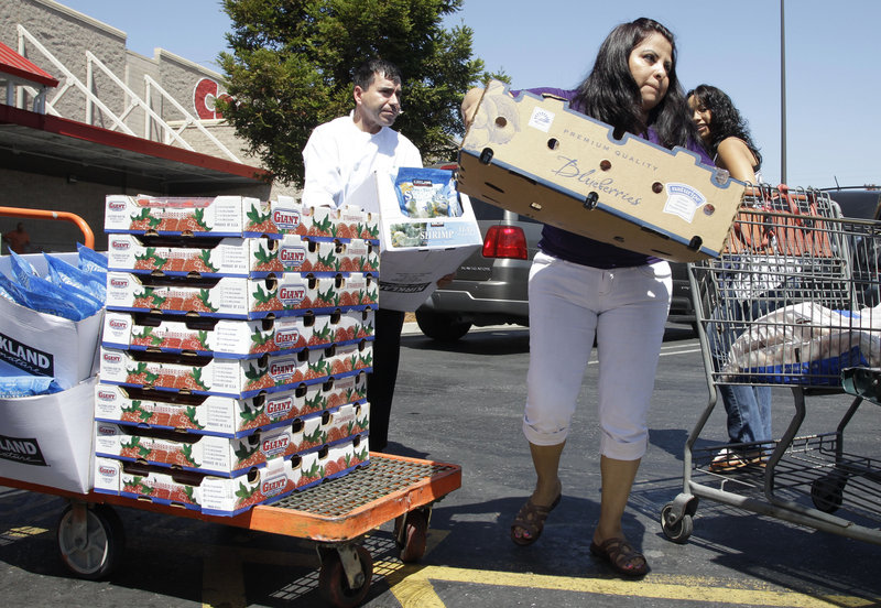Shoppers unload their purchases at a Costco store in Mountain View, Calif. Spending by U.S. consumers rebounded in July after declining in June for the first time in 20 months. Analysts say the increase points to a stronger third quarter, since consumer spending accounts for 70 percent of U.S. economic activity.