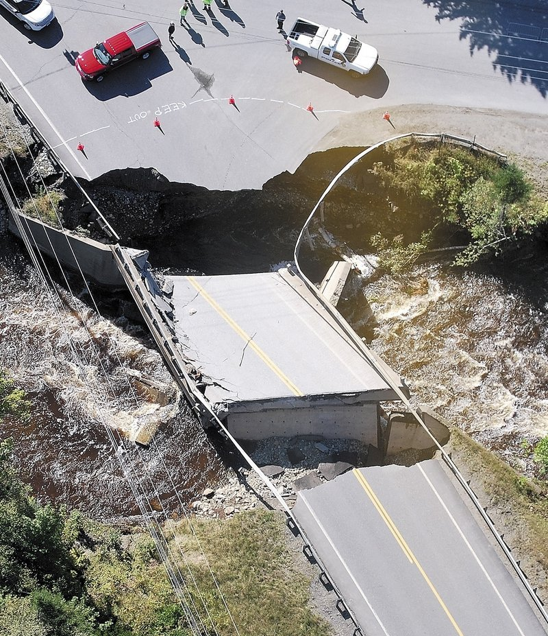 Gov. Paul LePage and other officials survey one of two washed-out bridges Monday on Route 27 in Carrabassett Valley. The damage temporarily cut off access to Sugarloaf Mountain.