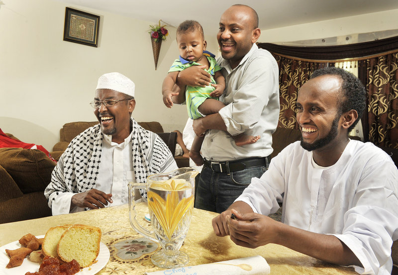Friends Yasin Atoor, left, Hamza Haadoow and his son, and Abdikadir Noor and their families gather to observe the end of Ramadan.