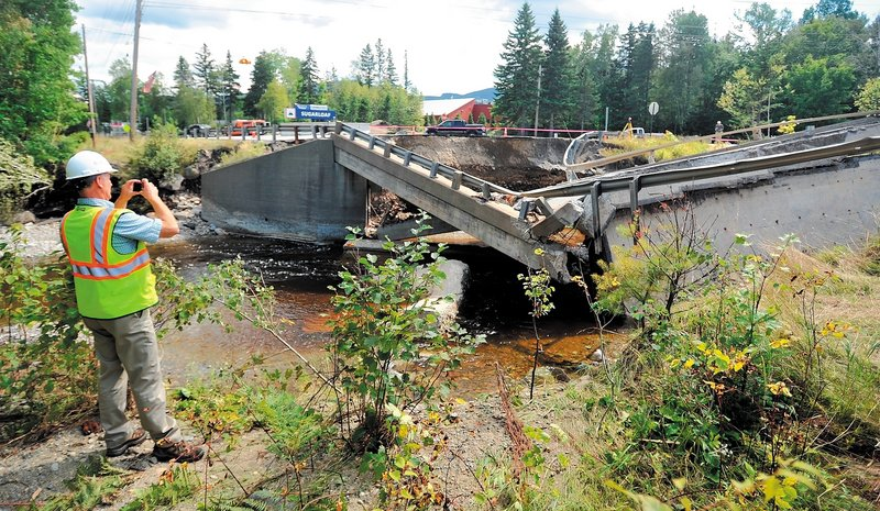 Ted Clark, a project manager for Reed & Reed General Contractors, assesses the damage to the bridge that failed on Route 27 in Carrabassett Valley during Sunday's storm. The bridge was to be repaired within the next 12 months because of a design flaw in its support system.