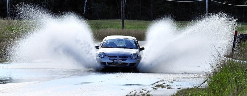 TROPICAL SPRAY: A motorist on Monday blasts through water where Route 16 in Embden is flooded from rain from Tropical Storm Irene.