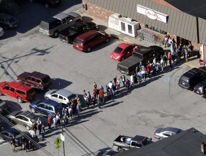 Residents stand in line outside a grocery store today in Rochester, Vt. The town has been completely cut off since Tropical Storm Irene hit.