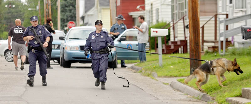 SEARCHING FOR A SUSPECT: A Maine State Police K-9 unit searches along LaSalle Street for the man that robbed the Winslow Community Federal Credit Union on nearby Monument Street Thursday morning.