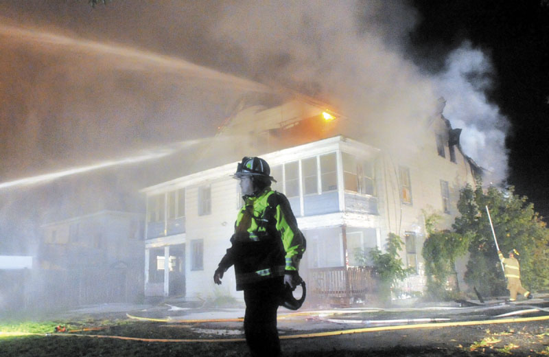 ON THE JOB: Waterville Fire Chief Dave LaFountain stands in front of a three-story apartment building as it burns Monday night on Water Street in Waterville. LaFountain is concerned about new policies from the State Fire Marshal's office due to budget cuts that scales back cases that fire investigators respond to.