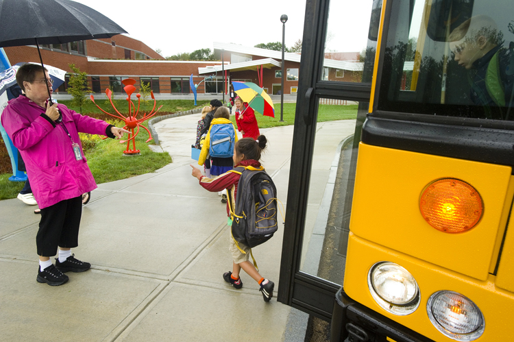 Students return to the Ocean Avenue Elementary School today as Portland schools opened for the new school year. Loretta Smith, an ed. tech. at the school, greets students arriving by bus.