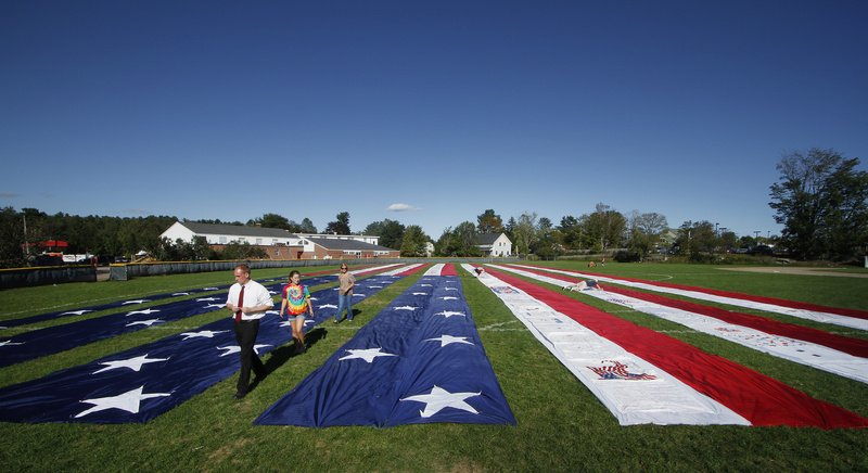 """A half-acre section of the Heart of America Quilt is displayed outside Freeport High School on Saturday. The quilt, which was started in Maine and includes signatures and messages from all 50 states and 14 countries, honors victims of the 9/11 attacks and serves as a symbol of national unity. More in today's Special section: """"Remembering 9/11"""""""