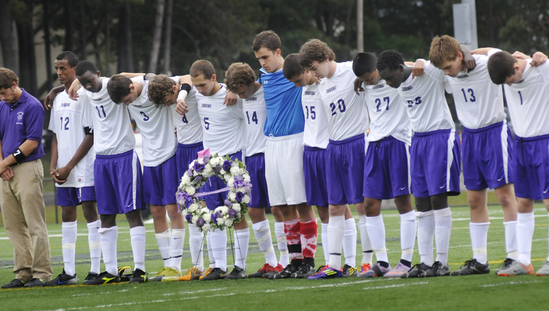 Deering High School's soccer team stands together during a moment of silence in memory of their teammate, 17-year-old senior Mohamed Hassan, who drowned Saturday while swimming with friends in the Presumpscot River off Allen Avenue Extension in Falmouth. The remembrance took place at Deering's game Thursday against Noble High School in Portland. The wreath was a gift from the Noble team.