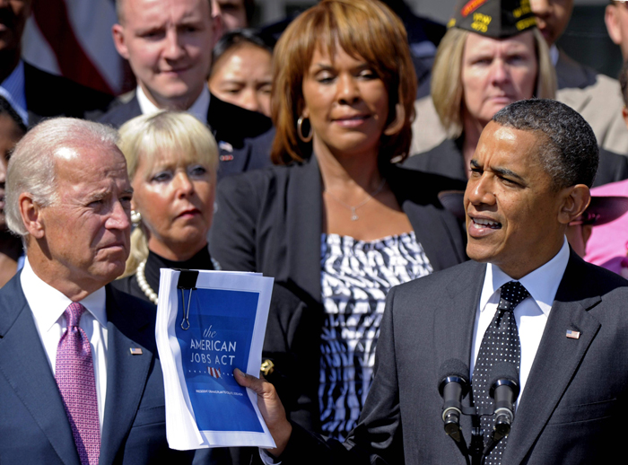 President Barack Obama, accompanied by Vice President Joe Biden, and others, holds up a copy of his American Jobs Act during a statement in the Rose Garden of the White House today.