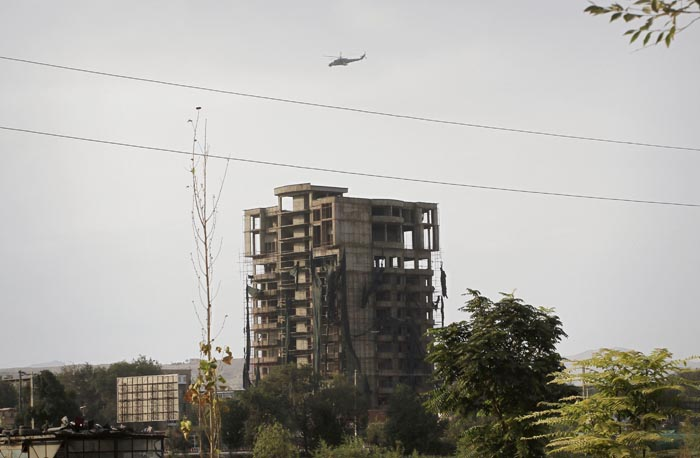 An Afghan military helicopter flies around a building occupied by militants in Kabul today.