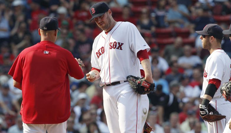 John Lackey hands the ball to Manager Terry Francona as he is taken out of the game against the Toronto Blue Jays in the sixth inning today at Fenway Park. The reeling Red Sox lost for the sixth time in seven games as the Blue Jays took a 5-4 win.