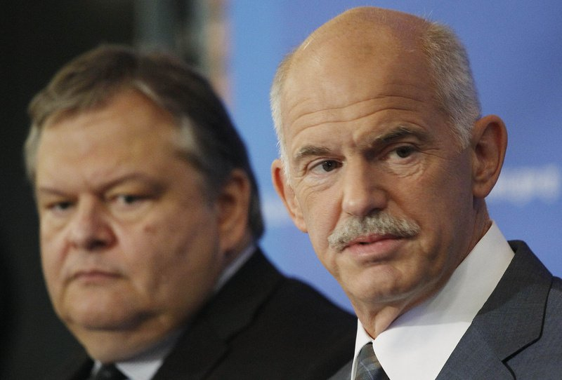 Greek Prime Minister George Papandreou, right, backed by his Finance Minister Evangelos Venizelos, speaks during a news conference in Thessaloniki, Greece on Sunday. Greece's cash-strapped government said Sunday it would impose a new property tax, on top of existing austerity measures, to contain this year's revenue shortfall and achieve a primary surplus in 2012.