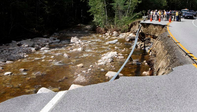 In this Aug. 31, 2011, photo, New Hampshire Gov. .John Lynch, among the crowd, inspects a section of the Kancamagus Highway where flash floods from Hurricane Irene washed out part of the road. The scenic highway through the White Mountains has been reopened.