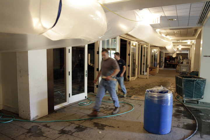 Workers walk through the flood-damaged basement conference center of the Woodstock Inn, which has closed for the month of September for repairs and cleanup.
