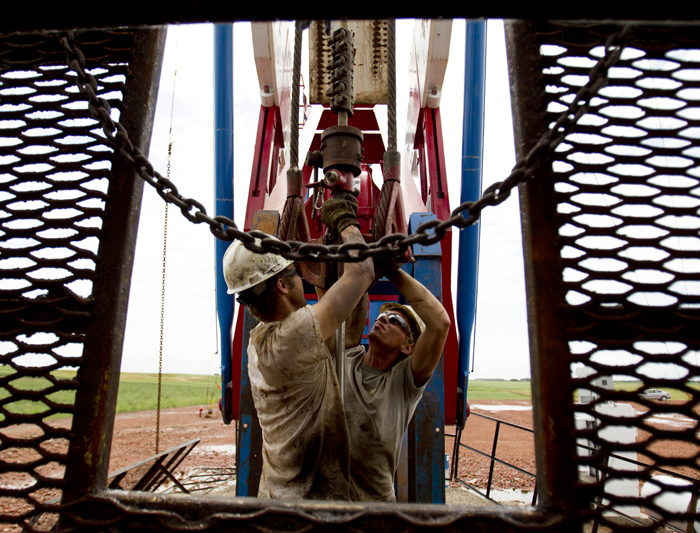 "Austin Mitchell, left, and Ryan Lehto, work on an oil derrick outside of Williston, N.D. With what many are calling the largest oil boom in recent North American history, temporary housing for the huge influx of workers, known as ""man camps,"" now dots the sparse North Dakota landscape."