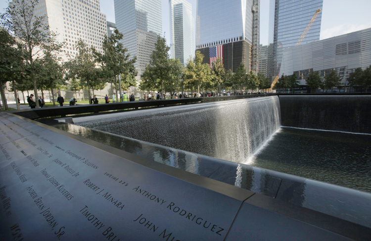 Visitors stroll the grounds near one of the pools at the 9/11 memorial plaza in the World Trade Center site in New York today.