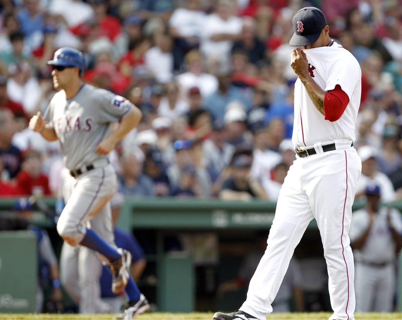 Boston Red Sox relief pitcher Felix Doubront, right, wipes his face after giving up a bases-loaded walk to Texas Rangers' Esteban German, allowing David Murphy, left, to walk home and score a run during the sixth inning on Sunday.