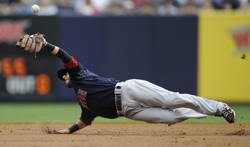 Dustin Pedroia of the Red Sox can't catch the ball during the first inning of the first game today against the Yankees at New York. The Red Sox lost, 6-2.