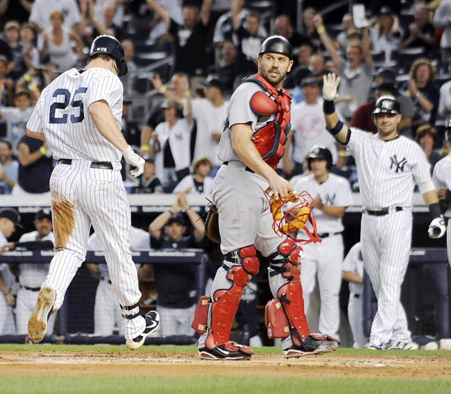 New York Yankees runner Mark Teixeira, left, scores as Boston Red Sox catcher Jason Varitek, front right, looks on during the first inning of the second game of a baseball doubleheader on Sunday at Yankee Stadium. Teixeira hit a two-RBI double and scored on a throwing error by Varitek.
