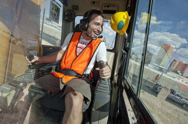 Grayson Cox, of Austin, Texas, works the controls of an excavator while learning to use construction equipment at Dig This in Las Vegas. For a few hundred dollars, tourists spend a few hours at Dig This pushing around dirt, one-ton tires and rocks that don't move when you kick them.