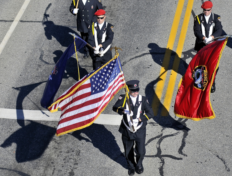 Staff photo by Michael G. Seamans Color Guard from the Winslow Fire Department lead the parade down Main Street in Waterville Saturday morning to remember the September 11th attacks 10 years later.