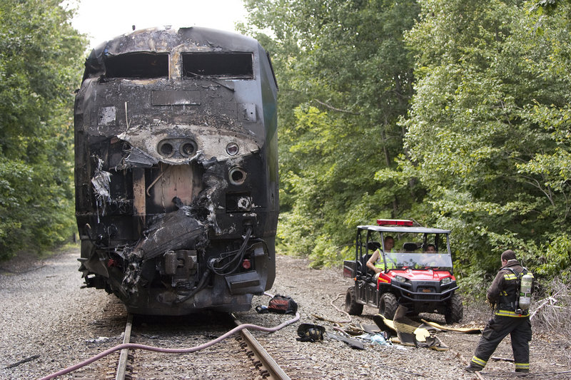 In this July 12, 2011, photo, the charred hulk of an Amtrak Downeaster engine sits on the tracks near the scene of a collision with a tractor-trailer.