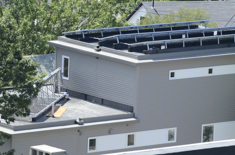 This rooftop view, taken from the nearby Portland Observatory, shows solar panels on the right and a side view of heating tubs on the left.