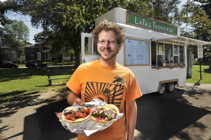 """Lola's Taqueria owner Jonathan Holmes shows a couple of his taco specials, including the """"Barbacoa,"""" a beef taco, and the """"Carnitas,"""" a pork version."""