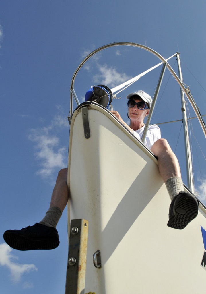 Karen Packard of Westbrook works on her sailboat, Room 25, after removing it from the waters off East End Beach in Portland as Hurricane Irene moved up the coast.