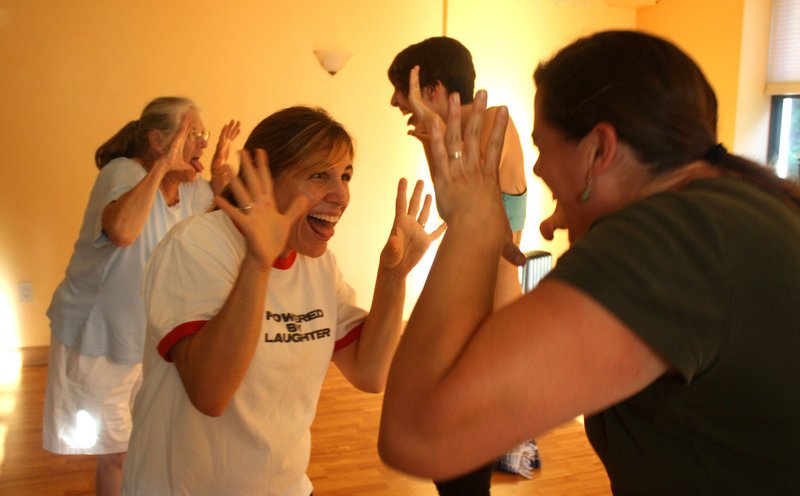 Laughter yoga instructor Katie West, founder of the Levity Project, goes one on one with a class member at a recent session at the Yogave studio on Route 1 in Falmouth.