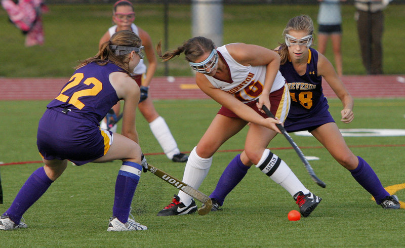 Mary Brown of Thornton Academy, center, looks for a way to control the ball around defense applied by Sarah LaQuerre, left, and Staci Swallow of Cheverus during Cheverus' 5-0 victory.